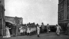 Ряд солдат, слева, целиться на одинокую фигуру, справа, в то время (в центре) офицер поднимает свой меч в качестве сигнала.  Взволнованный женщина, крайняя левая, поворачивает ее лицо со сцены.