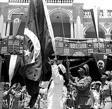 A man in military uniform raising a flag up a pole. Behind him are other uniformed men and others wearing traditional, civilian dress