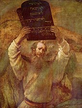This is an image of an oil on canvas picture by Rembrandt (1659) of a bearded man representing Moses with two tables of stone of the ten commandments held high in both hands.