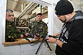 Romanian Land Forces Maj. MihaI Irminia, left, and Cpl. Ilie Zamfir, center, are briefed by an equipment instructor on how to mount a multiple integrated laser engagement system on an AK-74 rifle during 130305-A-ZD093-003.jpg
