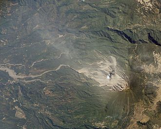 Santa María (volcano) - Steam rises from Santiaguito. The area of the flank destroyed by the 1902 eruption can be clearly seen. Lahar deposits snake down river valleys to the left of the image
