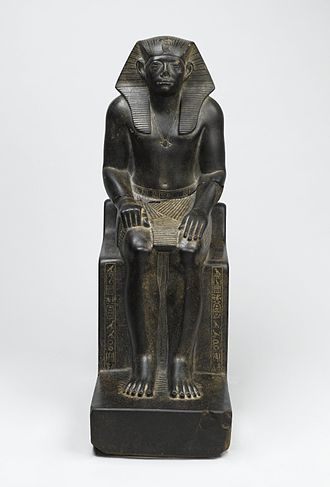 Senusret III - Granite statue of Senwosret III - he is shown wearing the nemes headcloth with a cobra image of Wadjet at the front, the pleated shendyt kilt, and the bull's tail, visible between his legs; beneath his feet are nine bows, symbolizing Egypt's traditional enemies under his power; unlike his predecessors, who were shown with idealized facial features, Senwosret has heavily lidded eyes, lined and haggard cheeks, and pursed lips; the reason for this stylistic change is not known, but imitations of his features by later kings and private individuals suggest that Senwosret's features were intended to convey his virtuous qualities. Brooklyn Museum
