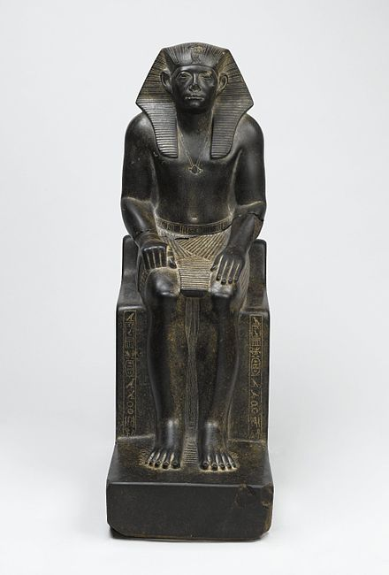 Granite statue of Senwosret III - he is shown wearing the nemes headcloth with a cobra image of Wadjet at the front, the pleated shendyt kilt, and the bull's tail, visible between his legs; beneath his feet are nine bows, symbolizing Egypt's traditional enemies under his power; unlike his predecessors, who were shown with idealized facial features, Senwosret has heavily lidded eyes, lined and haggard cheeks, and pursed lips; the reason for this stylistic change is not known, but imitations of his features by later kings and private individuals suggest that Senwosret's features were intended to convey his virtuous qualities. Brooklyn Museum Senwosret III, ca. 1836-1818 B.C.E. Granite.jpg