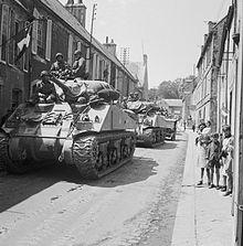 Chars M4 Sherman et Jeep du 30e corps d'armée britannique traversant Bayeux en 1944, pendant la bataille de Normandie.