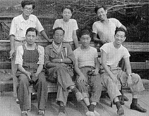 Shinichiro Sakurai - Shinichiro Sakurai (second from left sitting) and his boss Takuya Himura (leftmost standing) at the Mitaka Plant of the Prince Motor Company circa 1954.