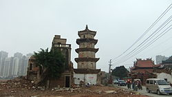 Surviving White Pagoda (center) of Shuixin Chan Temple (right), with the adjacent old residential neighborhood (left) demolished, to make way for new development (such as seen in the background)