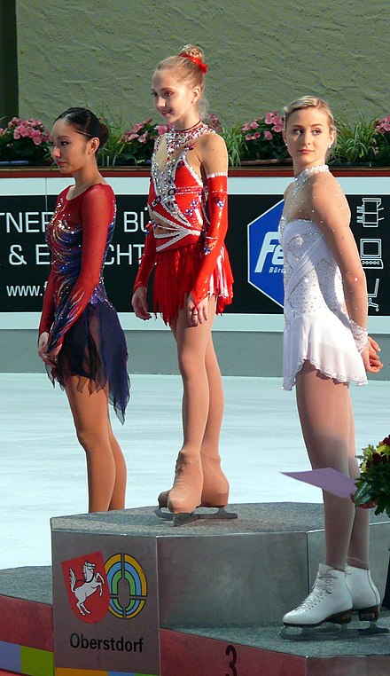 Ando, Radionova, and Cain stand on the ladies' podium