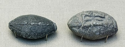 "Ancient Greek lead sling bullets with a winged thunderbolt molded on one side and the inscription ""DEKsAI"" (""take that"" or ""catch"") on the other side Sling bullets BM GR1842.7-28.550 GR1851.5-7.11.jpg"