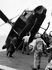 South Vietnamese helicopter is pushed over the side of the USS Okinawa during Operation Frequent Wind, April 1975