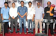 Nani, Sanjeev Lamba, Ajay Devgan, Rajamouli, Keeravani and Suresh Babu stand and look towards the camera.