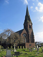 The west end, with a rose window, and the steeple of a Gothic style church, with a clock face; gravestones in the foreground and a leafless tree to the left.