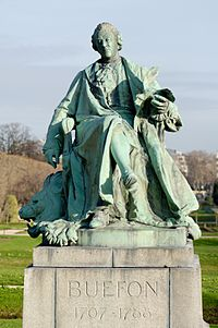 Bronze statue of Buffon wearing a ruffled shirt and a long coat, holding a bird with wings spread.