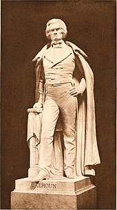 Life-sized statue, standing with full cloak to ankles, left hand on hip, right hand on book, serious and distinguished demeanor