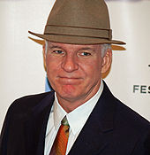 A man wearing a suit, a multi-colored tie, and a tan hat.
