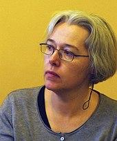 Fotografia de uma mulher com cabelo grisalho e óculos.