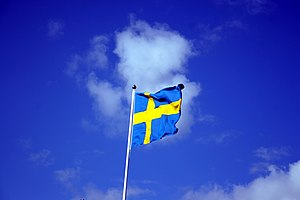 Swedish flag with blue sky behind.jpg