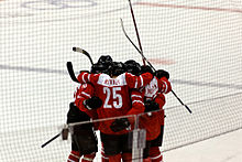 A group of hockey players stand on the ice in a circle, hugging each other and celebrating. They are all wearing red and white sweaters.
