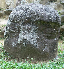 A low standing stone protruding from short grass, with the stonework of a structure visible behind it. The upper portion of the stone has a raised area perhaps representing a cap or helmet. Below this are carved two eyes in the form of circles divided by a horizontal line, giving the appearance of being closed. The cap and the area between the eyes are covered with pale lichen