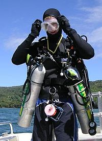 The front view of a standing diver ready for the water is shown. He is carrying a sling mounted aluminium cylinder on each side, clipped to a chest D-ring and a hip D-ring.