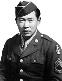 Head and torso of a serious faced man wearing a garrison cap and a military jacket with bright buttons and a patch and stripes on the upper sleeve.
