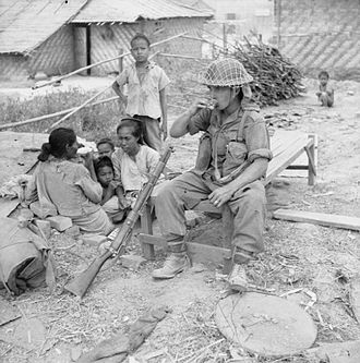 Battle of Meiktila and Mandalay - A Burmese family living in a dug-out share tea with a British soldier in Meiktila, 10 March 1945.