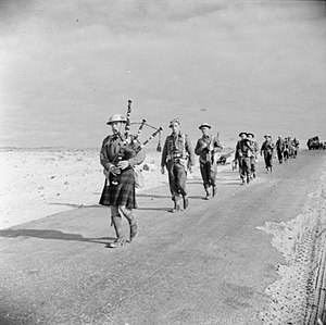 Douglas Wimberley - A piper of the 5th Battalion, Queen's Own Cameron Highlanders leading his comrades along the road near El Aghelia, 19 December 1942.