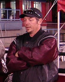 Half-length view of a person in his early 40s. He is standing upright with his arms folded across his chest. He is wearing a black and maroon coat and a baseball cap.
