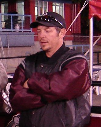 Theoren Fleury -  alt=Half-length view of a person in his early 40s. He is standing upright with his arms folded across his chest. He is wearing a black and maroon coat and a baseball cap.