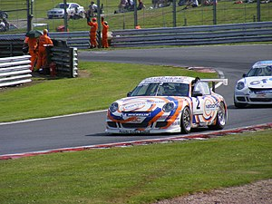 Redline Racing - Tim Harvey waves to the Oulton Park crowd after taking second place during round 13 of the 2008 Porsche Carrera Cup Great Britain