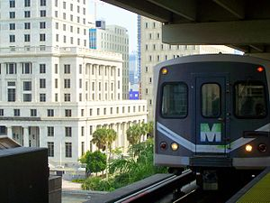 Government Center station (Miami) - A Metrorail train is approaching the upper level of the Government Center station with the Dade County Courthouse in the background.