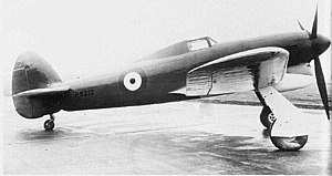 "Hawker Typhoon - The unarmed first prototype Typhoon P5212 taken just before its first flight. The prototype had a small tail unit and a solid fairing behind the cockpit, which was fitted with ""car door"" style access hatches; no inner wheel doors were fitted and the Sabre engine used three exhaust stubs either side of the cowling."
