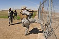 U.S. Air Force Senior Airman Kathleen Stenger, right, kicks a security fence to test it as Senior Airman Jennifer Marshik, both with the 219th Security Forces Squadron (SFS), North Dakota Air National Guard 130522-Z-WA217-592.jpg