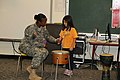 U.S. Army Sgt. Jamara Ross, left, assigned to the 10th Regional Support Group, Support Operations and Maintenance, works with a kindergarten student in the Bob Hope Primary School, during a music lesson 131120-A-LG030-815.jpg