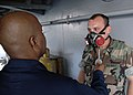 US Navy 060607-N-0938S-017 Aviation Ordnanceman 1st Class Timothy Irby puffs smoke at Culinary Specialist conducts respirator fit test training with a crewmember aboard the amphibious assault ship USS Saipan (LHA 2).jpg