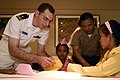 US Navy 071127-N-4010S-095 Lt.j.g. Alex Sicola, assigned to the amphibious assault ship USS Essex (LHD 2), and 1st Lt. Jason Shin, assigned to the Command Element of the 31st Marine Expeditionary Unit (MEU), assist children fro.jpg
