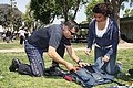 US Navy 090401-N-5366K-005 Special Warfare Operator 1st Class (SEAL) Aaron Darakjy, assigned to the U.S. Navy Parachute Team, show a student how to pack a parachute at Granada Hills Charter High School.jpg