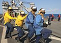 US Navy 100413-N-1082Z-144 Hose handling team members step in unison as they simulate putting out a Flight Deck fire during an emergency flight quarters drill.jpg