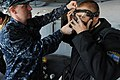 US Navy 111022-N-RB564-019 Hull Technician Fireman Justin Whipple shows Ukrainian Seaman Michel Mnua how to adjust the facemask on a self-contained.jpg