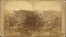 Two identical photos of a street, crowded with various horse-drawn wagons, with large storage tanks on either side and oil derricks visible in the distance. The images are mounted side-by-side on a card.