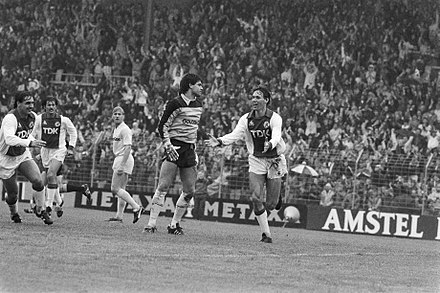 Van Basten celebrates his goal for Ajax to give the team a 2-0 lead in an eventual 8-2 win against Feyenoord in September 1983, following Gerald Vanenburg's corner. Edo Ophof (Ajax), Felix Gasselich (Ajax), Andre Hoekstra (Feyenoord) and goalkeeper Joop Hiele (Feyenoord) are the other players in the picture. The average age of the Ajax team at the time was roughly 22 1/2 years. Van Basten (r) juicht na zijn treffer (2-0), midden Feyenoorddoelman Hiele, Bestanddeelnr 932-7028.jpg