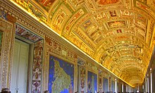 Photo of a long wide corridor filled with a crowd of people in casual dress.VATICAN MUSEUMS