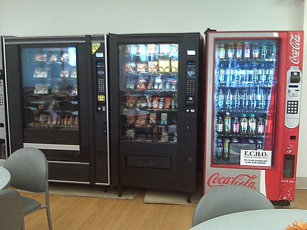 A full line of vending machines in a hospital cafeteria, including machines for drinks, snacks, and microwaveable foods Vending machines at hospital.jpg