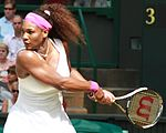 A black woman wearing a white ensemble with purple accents and headband