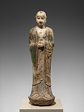 Colored limestone sculpture of monk holding unidentified object