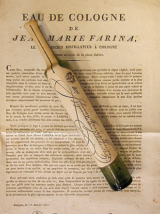 Johann Maria Farina gegenüber dem Jülichs-Platz - Original Eau de Cologne – The Rosoli bottle is the first to have been produced by Farina House. The instruction leaflet in French is in the background. The slim green bottle had to be stored in a horizontal position because it was corked. Until 1832, Eau de Cologne was only sold in Rosoli bottles.