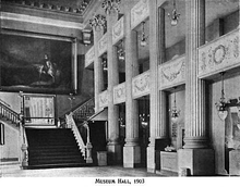 Black-and-white photo of a two-story interior room. There are large columns on the right-hand wall and a wide staircase on the back wall. A large painting hangs above the staircase landing.