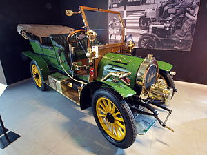 Genevieve (film) - The 1905 Spyker 12/16-HP Double Phæton that was used as Ambrose Claverhouse's car in the film. As of 2012 this car is held in the Louwman Museum in the Netherlands, along with Genevieve. A still from the film can be seen in the background