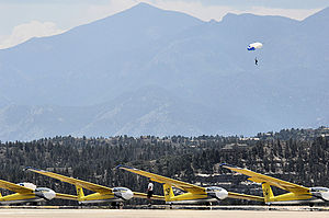 306th Flying Training Group - Cadet parachuting out of airplanes over a lineup of gliders