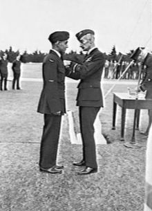 Full-length picture of two men in dark military uniforms facing each other