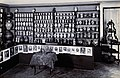 A long wall in a room with decorated pharmacy jars on shelve Wellcome V0029792.jpg